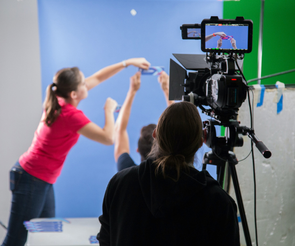 Two people in front of a green screen holding up a product while a videographer films
